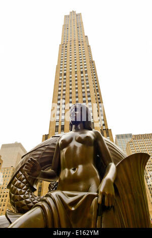 Manhattan, New York, U.S. - May 21, 2014 - At Rockefeller Plaza is bronze Mankind statue, Maiden, by artist Paul Manship, with 30 Rockefeller Center looms behind, during a pleasant Spring Day, though skies are cloudy. - Stock Image