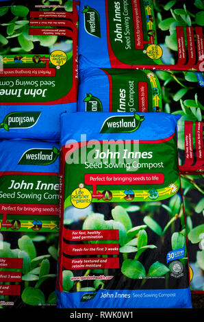 A stack of bags of John Innes seed sowing Compost in a garden centre labelled Perfect for bringing seeds to life - Stock Image