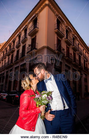 Newlywed couple poses in front of a building in a European city - Stock Image