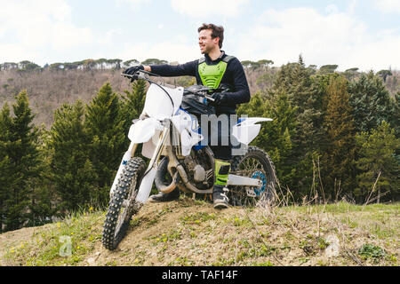 Portrait of confident motocross driver on circuit - Stock Image