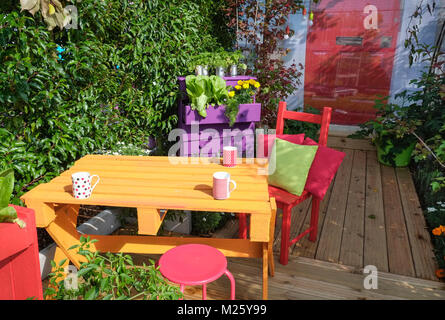 Small outdoor garden patio area, with bright colour dining table and chairs. - Stock Image