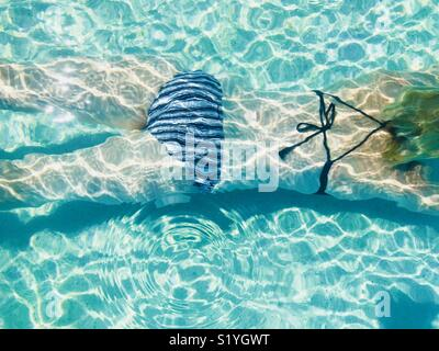 A women swimming underwater in a pool shot from above. Intercontinental hotel, Fiji. - Stock Image
