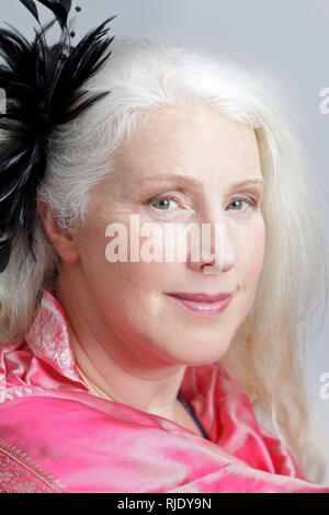 Glamour portrait of an attractive mature woman with gray hair wearing a pink scarf and a black feather fascinator. - Stock Image