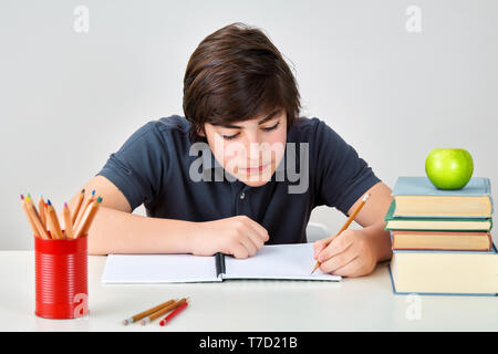 Caucasian teenager boy sitting at the table writing to his notebook. Kid doing homework. - Stock Image