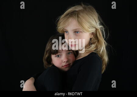 Two girls in an embrace missing a loved one - Stock Image