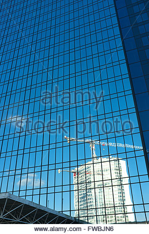 Reflection in office block windows of another tower block and construction site tower cranes. Birmingham city, UK. - Stock Image