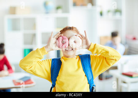 Cheerful schoolgirl with backpack holding two donuts in front of her eyes while having fun - Stock Image