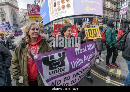 London, UK. 9th Dec, 2018. People carry a Unite Against Fascism banner on the united counter demonstration by anti-fascists in opposition to Tommy Robinson's fascist pro-Brexit march. The march which included both remain and leave supporting anti-fascists gathered at the BBC to to to a rally at Downing St. Police had issued conditions on both events designed to keep the two groups well apart. Credit: Peter Marshall/Alamy Live News - Stock Image
