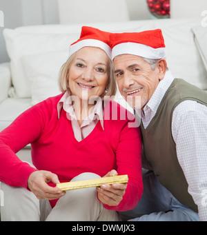 Smiling Senior Couple With Christmas Present - Stock Image