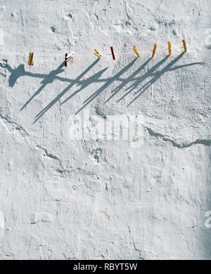a line of wooden pegs on a rope washing line running across the top half of the image the wooden pegs are clipped onto the line in regular intervals,  - Stock Image
