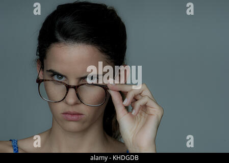 Young woman looking over the top of her eyeglasses, frowning, portrait - Stock Image