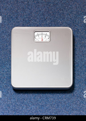 Silver weighing scales on a blue carpet background - Stock Image