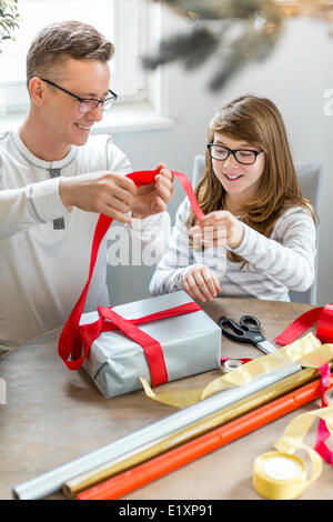 Happy father and daughter wrapping Christmas present at home - Stock Image