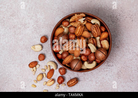 mix of nuts in a wooden bowl on a light background. view from above - Stock Image