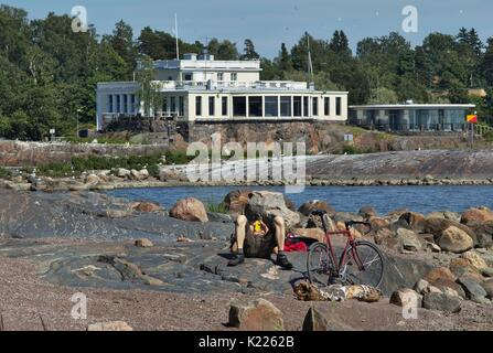 Bicyclist relaxing on rocky beachfront with large boulders. House with panorama windows in background - Stock Image