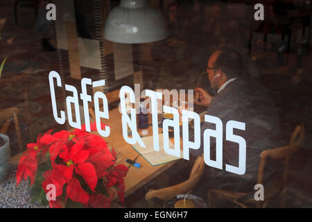 Cafe and Tapas sign on window with diner eating inside - Stock Image