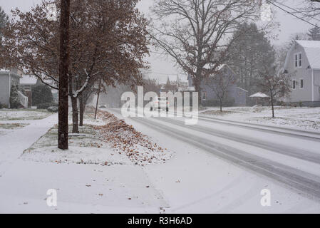A car travels on a snow-covered roadway in Pennsylvania, USA. - Stock Image