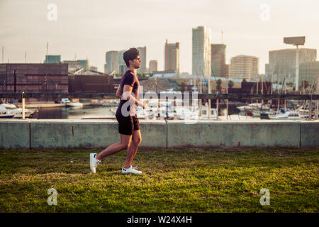 Young athletic man running at park with skyscrapers background - Stock Image