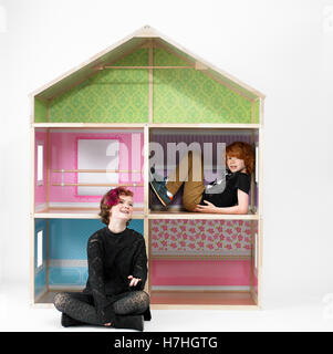 Teen girl and school boy playing in a giant doll house - Stock Image