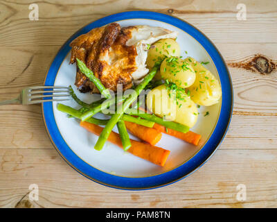 Lunch  a quarter roast chicken  with new potatoes carrots, green beans and chopped chives on a wooden table top - Stock Image