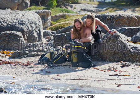 Couple preparing scuba equipment for a dive from the beach - Stock Image