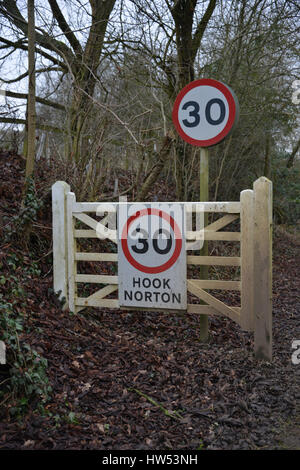30mph speed limit sign and signpost on the way into the north Oxfordshire village of Hook Norton - Stock Image