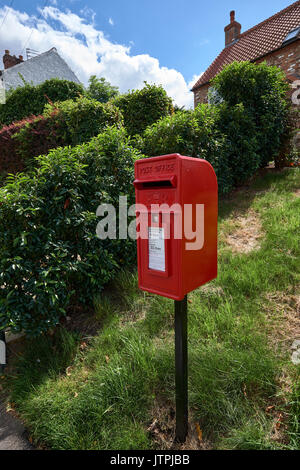 Red Royal Mail post box postbox in Nether Poppleton, York, United Kingdom with collection times visible. - Stock Image
