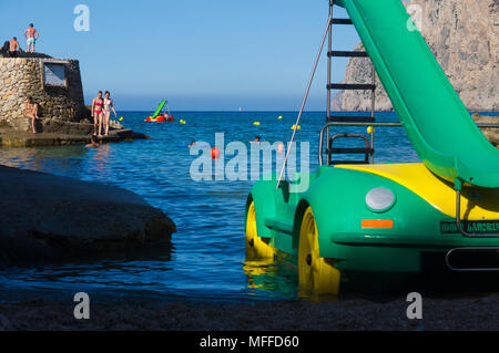 People enjoy the water at Cala San Vicente within sight of a pedalo parked close to shore in Mallorca, Spain. - Stock Image