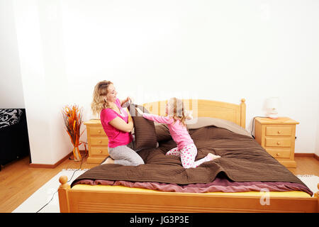 Happy family fighting with pillows indoors - Stock Image