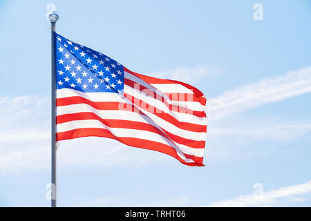 American flag on flagpole against blue cloudy sky - Stock Image