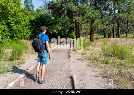 Man hiking walking on Main Loop trail path in Bandelier National Monument in New Mexico during summer in Los Alamos - Stock Image