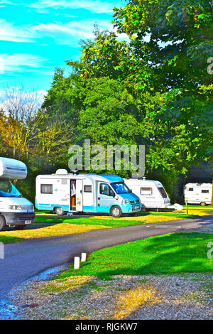 Touring units on site at the Caravan & Motorhome Club site at Cirencester Park, in the Cotswold district of Gloucestershire. Autumn sunshine. - Stock Image