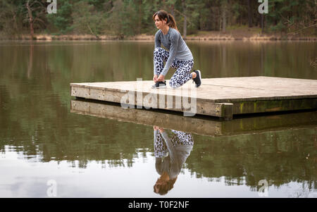 woman runner tying her shoe laces preparing for a run by a lake - Stock Image
