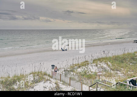 Family and people relax on the white sand Florida secluded gulf coast beach at Orange Beach an Alabama panhandle resort town, USA. - Stock Image