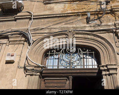 Detail from house exterior in Nicosia Cyprus showing an array of cables and power lines disturbing the view of a stone facade with arched carvings - Stock Image