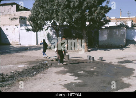 Street scene, people collecting water from a well with buckets; Bukhara, Uzbekistan, former USSR. - Stock Image