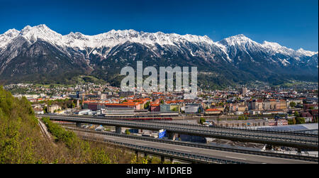 Nordkette massif, covered with snow in late April, over Innsbruck, elevated section of Inntal Autobahn in foreground, - Stock Image