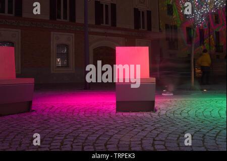 illuminated modern bench on cobblestone street at night - Stock Image