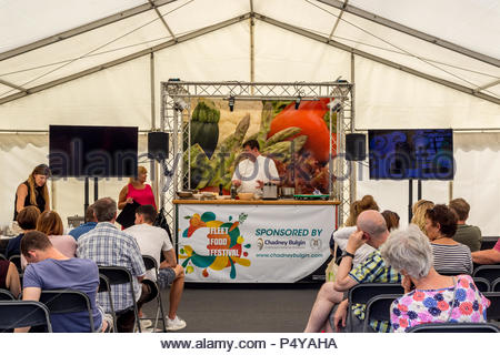 Visitors enjoying the sunshine at Fleet Food Festival 2018. Adam Fargin, head chef at the nearby Four Seasons Hotel presents modern classical cooking - Stock Image