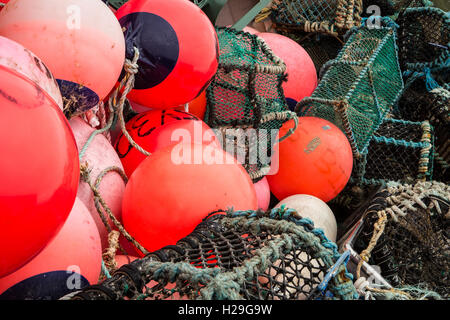 a tangled heap of bright orange/red fishing floats and creels - Stock Image