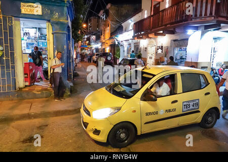 Cartagena Colombia Old Walled City Center centre Getsemani night nightlife Hispanic resident residents street corner doorway car taxi cab yellow - Stock Image