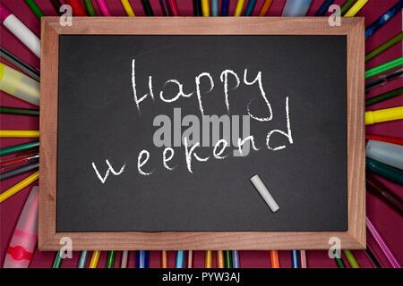 Education concept. HAPPY WEEKEND written on blackboard, chalkboard - Stock Image