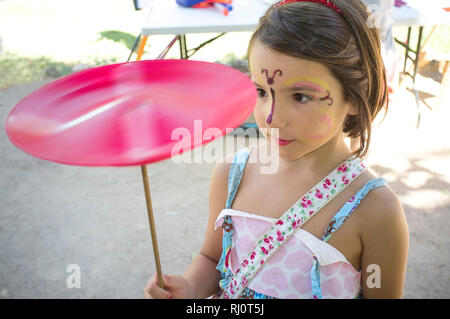 Face painted child girl playing with spinning plate. Classic toys concept - Stock Image