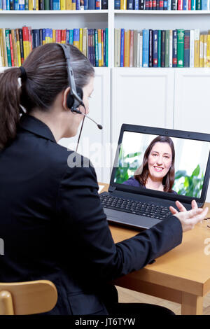 Head of the human resources department with headset and computer in her office, carrying out a video call job interview with a young female applicant - Stock Image