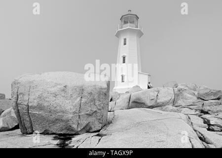 Lighthouse and rocky shoreline  Peggy's Cove Nova Scotia Canada - Stock Image