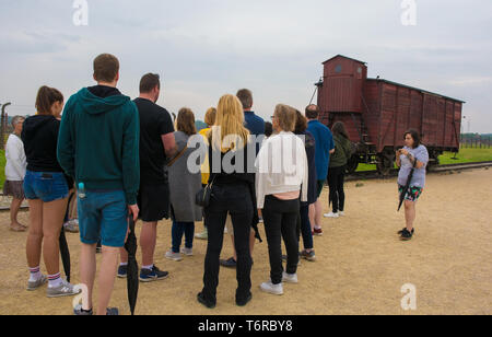 Oswiecim, Poland - July 11th 2018.  A tour group crowds around their guide as she explains about the Train Wagon on the unloading platform at the Birk - Stock Image