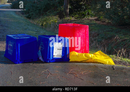 Empty upside down Blue Box recycling bins at curbside with a red bin for plastics and a yellow bag for cardboard. - Stock Image