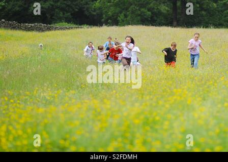 Running kids in a field with flowers - Stock Image