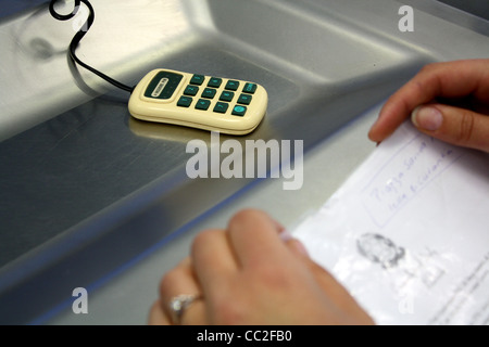 Woman waiting at cashier desk about the enter pin number into small machine - Stock Image