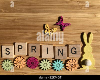Spring, in wooden letters on wood background with flowers, butterflies and a rabbit - Stock Image